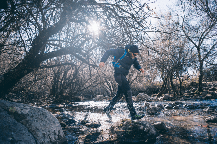 trail running in winter through a river